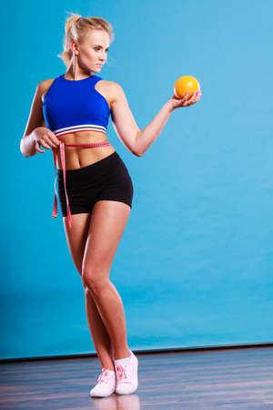 Time for diet slimming weight loss. Health care and healthy nutrition. Young fitness woman fit girl with measure tape and grapefruit on blue