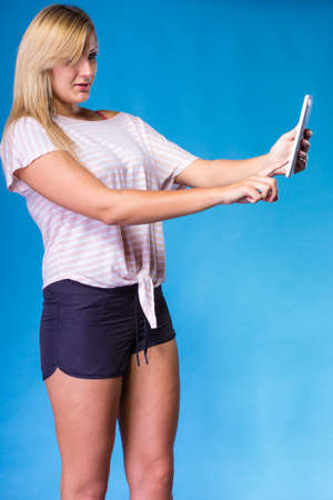Modern devices, social media, photography concept. Blonde woman taking self picture, selfie, with tablet. Studio shot on blue background Stock Photo