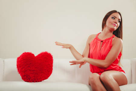 red sofa: Sad unhappy young woman girl with red heart shape pillow sitting on white sofa couch. Valentines day love.
