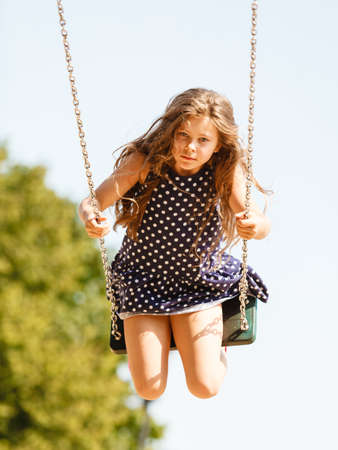 Have fun and leisure concept. Long haired enjoyable girl swinging outdoor in garden playground. Lovely child playing on swing-set. Stock Photo