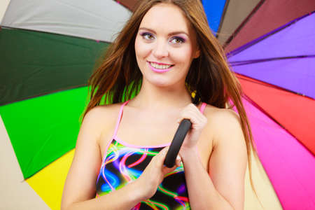 Fashion, great outfits for summer concept. Happy woman with long brown hair posing in swimsuit and colorful umbrella