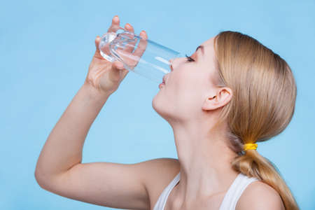 Food, health concept. Woman holding glass of orange flavored drink and drinking from it. Studio shot on blue background