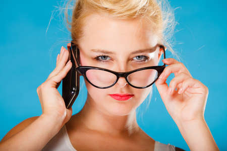 Librarian, accountant and secretary concept. Retro, pin up style. Young blonde woman looking through glasses. Girl holding smartphone on blue background in studio. Stock Photo