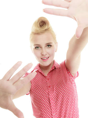 Hand gesture concept. Retro pin up woman wearing red short shirt having hands in front of face. Studio shot isolated