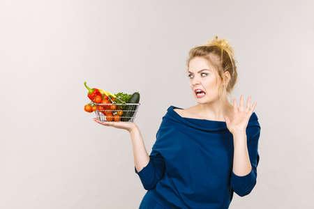 Mujer adulta no les gusta comer verduras, alimentos saludables, productos vegetarianos. Mujer sosteniendo cesta pequeña con verduras verdes, rojas cara expresión disgustado negativo, en gris Foto de archivo - 76777328