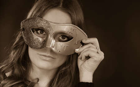 Holidays, people and celebration concept. Closeup woman face with carnival venetian mask on dark background, black and white photo Stock Photo