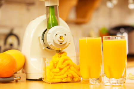 kitchen appliances: Making orange juice nutritious vitamin packed drink in juicer machine at home in kitchen. Healthy eating, vegetarian food, dieting concept