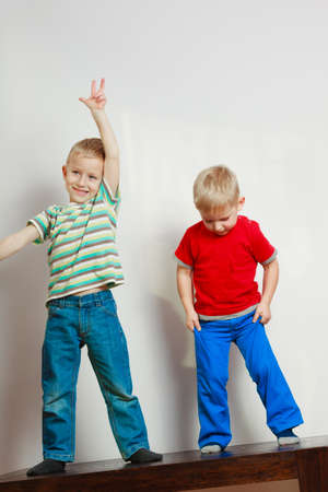 Childhood, relationship between brothers concept. Two little boys siblings playing together on table having fun. Stock Photo