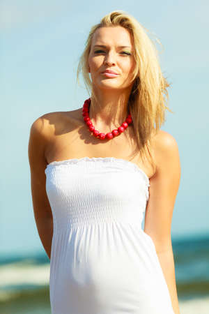 careless: Nature beach outdoors and female. Nice lady enjoying nature and beach. Young woman wearing long white dress and beautiful red necklace.