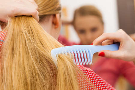 bathroom mirror: Woman combing brushing her long blonde smooth hair in bathroom, looking in mirror. Teen girl taking care refreshing her hairstyle in morning. Haircare concept.