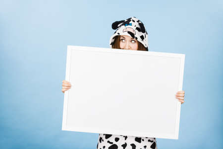 lady cow: Teenage girl in funny nightclothes, pajamas cartoon style covering her face with blank empty banner board. Advertisement copyspace.