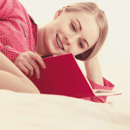 Girl lying in bed reading book. Young blonde female wearing red dotted pajamas relaxing at home on mattress. Toned filtered image