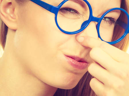Stinky smells, clogged concept. Nerdy woman in big funny glasses holding nose smelling bad scent