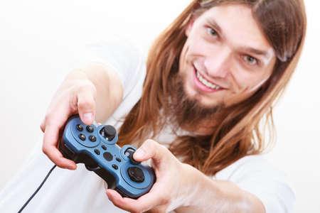 jugando videojuegos: Jugando juegos. hombre alegre sonriente joven del juego en PlayStation consola Xbox. Individuo con el joystick de la almohadilla.