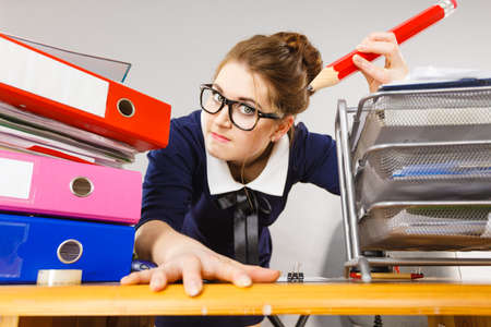 mobbing: Mobbing at work, bad job relations concept. Angry mad bossy businesswoman being furious sitting working at desk full off documents in binders.