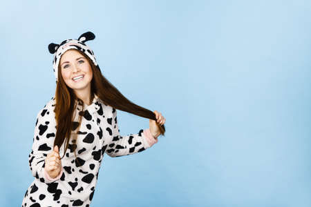 Happy teenage girl in funny nightclothes, pajamas cartoon style smiling, positive face expression, studio shot on blue.