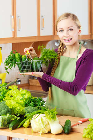 medula: Buying healthy dieting food concept. Woman in kitchen having many green vegetables holding small shopping basket trolley.