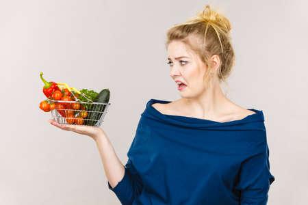 Mujer adulta no les gusta comer verduras, alimentos saludables, productos vegetarianos. Mujer sosteniendo cesta pequeña con verduras verdes, rojas cara expresión disgustado negativo, en gris Foto de archivo - 81044332