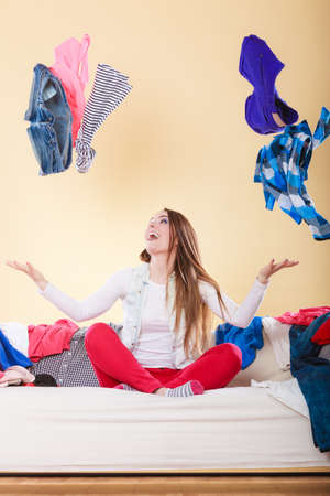 Happy woman sitting on sofa couch in messy living room throwing clothes. Young girl surrounded by many stack of clothing. Disorder and mess at home.