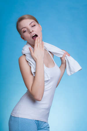 Tiredness, boredom concept. Sleepy woman placing hand on mouth yawning while holding towel on shoulder, studio shot on blue background