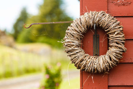 Handmade decorative objects concept. Rounded wicker decoration hanging on wooden wall