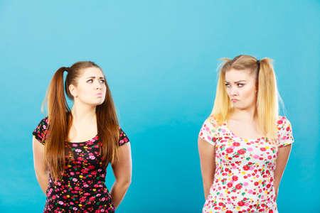 Twee jonge vrouwen worden beledigd door elkaar, krijgen de bult en staan achteruit Stockfoto