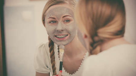 bathroom mirror: Skincare. Blonde woman in bathroom with gray clay mud mask on her face. Young lady taking care of skin. Spa beauty wellness. Filtered photo Stock Photo