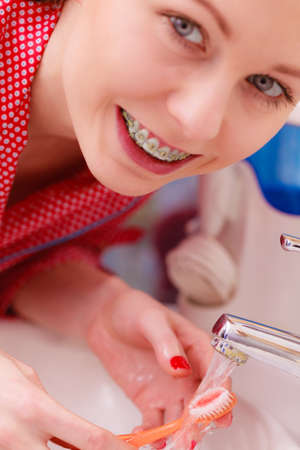 Woman brushing cleaning cavity in bathroom. Girl with teeth braces holds toothbrush, washing brush under running water. Oral hygiene. Stock Photo