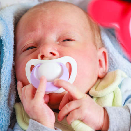 Infant care, beauty of childhood concept. Little newborn baby sleeping calmly in bed with teat in mouth. Zdjęcie Seryjne