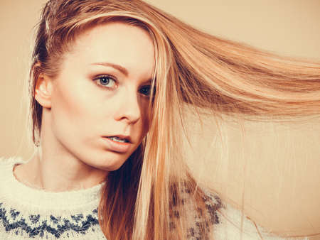tangling: Haircare, choosing best conditioner for tangled hairstyle concept. Teenage blonde girl brushing her hair with comb Stock Photo