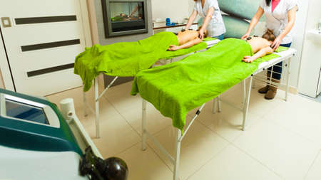 Spa relaxation, healthy pleasure concept. Two women lying on stomach having massage with hot rocks stones in beautician 免版税图像