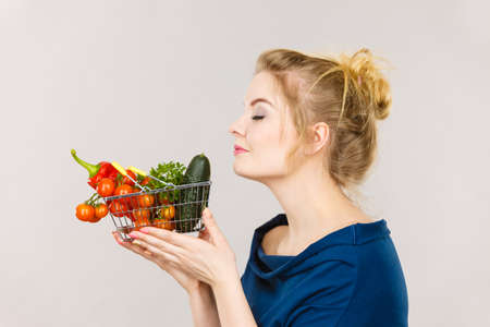 Buying good food, vegetarian products. Attractive woman holding shopping basket with green red vegetables inside, smelling with eyes closed, recommending healthy high fibre diet, on grey Banque d'images - 119869041