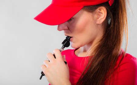 salvavidas: Prevención de accidentes y rescate acuático. Muchacha del primer en el equipo rojo del salvavidas de servicio que sopla un silbido en gris Foto de archivo
