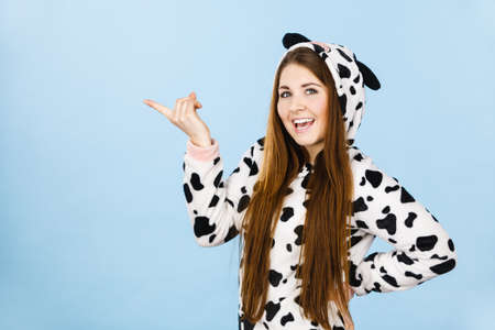 Happy teenage girl in funny nightclothes, pajamas cartoon style pointing at copy space with positive face expression, studio shot on blue. Advertisement concept Reklamní fotografie