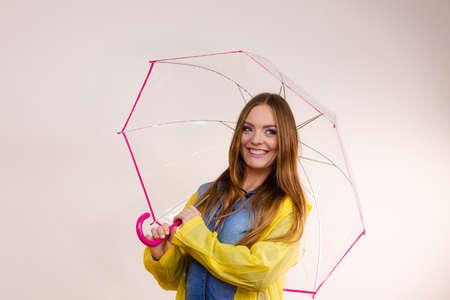 Woman rainy smiling girl wearing waterproof yellow coat standing under umbrella having fun. Meteorology, forecasting and weather season concept Stock Photo