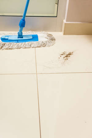Taking care of household equipment concept. Dirty floor with sand and cleaning mop standing next to it Foto de archivo