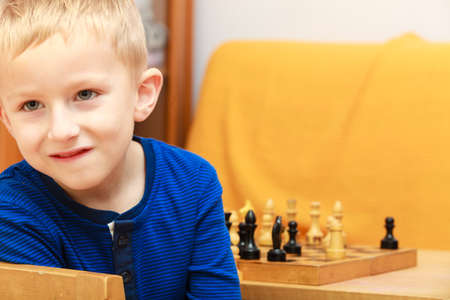 Intelligent, smart kids, games good for brain intelligence concept. Young kid boy playing chess and having fun.