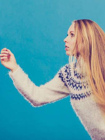 Weglopen van iets concept. Vrouw met lang blond haar uitgevoerd. Studio die op blauwe achtergrond is ontsproten. Stockfoto
