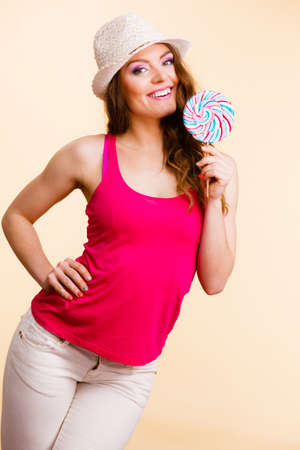 Beautiful woman wearing red tshirt summer hat holding big lollipop candy in hand. Sweet food fun concept. Studio shot on bright beige