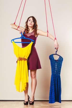 compras compulsivas: Shopaholic concepto de adicción a la moda. Adicto a la mujer de las compras, la marioneta marioneta chica con la ropa puesta, la compra de la cadena trastorno.