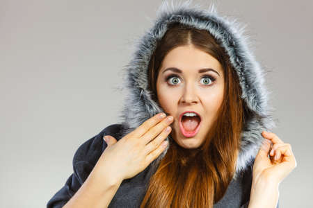 astonish: Shocked woman wearing dark poncho coat with furry hood. Winter fashion, trendy clothing outfits concept. Stock Photo