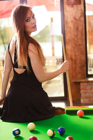 Fashion and fun concept. Young seductive girl posing by billiard pool. Sexy fashionable woman spending time on recreation.