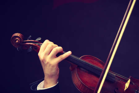 instrumentalist: Music passion, hobby concept. Close up young man man dressed elegantly playing on wooden violin. Studio shot on dark background Stock Photo