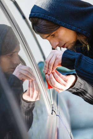 Anti theft system problem concept. Thieft man dressed in black holding screwdriver trying to break into car Stock Photo