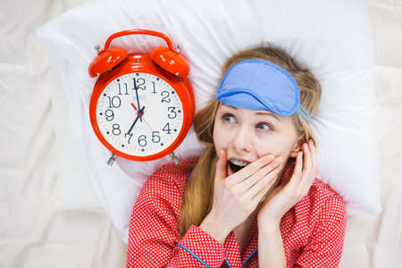 Shocked young woman being late wearing cute pink pajamas holding big red old fashioned clock showing time. Stock Photo
