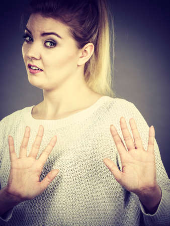 Woman having disgust face expression seeing unpleasant thing deny something showing stop gesture with open hands, grey background. Stock Photo