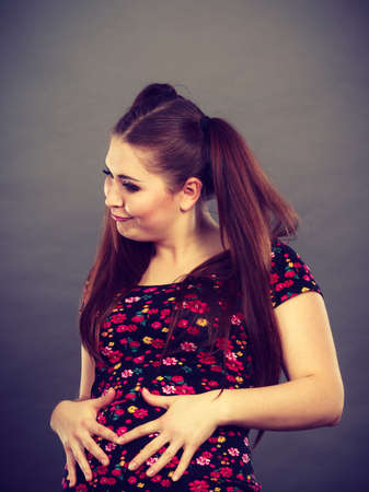 Funny teenage woman with ponytails holding their stomach having fun. Stock Photo