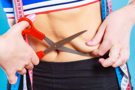 pinching: Weight gain diet liposuction concept. Woman with measure tapes pinches in the fat at the waist, holding scissors cut fold skin Stock Photo