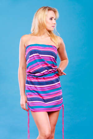 Summer trendy fashionable outfit ideas concept. Blonde woman wearing short colorful striped strapless dress