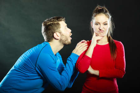 Husband apologizing wife. Man asking woman for forgivness. Boyfriend trying to convince girlfriend. Conflicted couple in studio on black. Relationship problem.